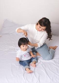 幸せな愛情のある家族。ママと子供の女の子はベッドで楽しんでいます。
