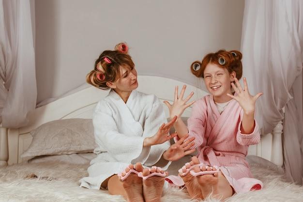 Счастливая любящая семья. мама и дочка делают маникюр, педикюр, делают макияж и развлекаются. мама и маленькая девочка в халатах и с бигуди на голове.