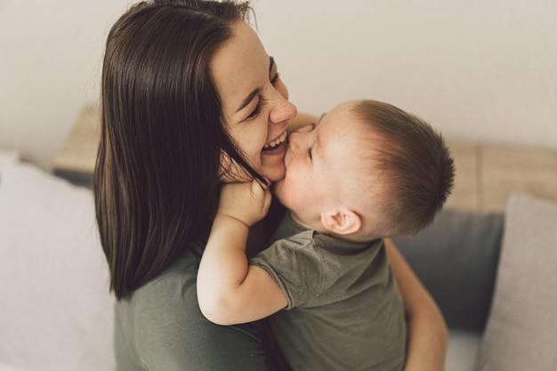 Счастливая любящая семья. мама и его сын обнимаются дома.