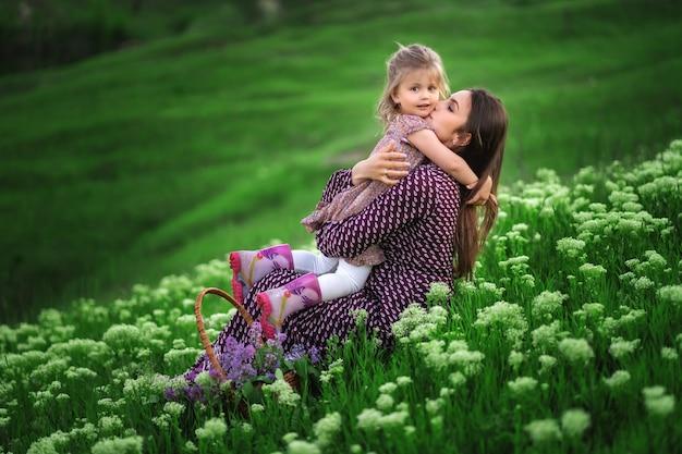 幸せな愛情のある家族の母親と女の赤ちゃんが遊び、キスしたり、抱き合ったりする