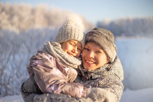 Счастливая любящая семья. мать и ребенок девочка весело, играя и смеясь над снежной зимой.