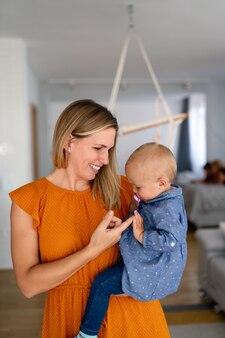 Счастливая любящая семья. мать и дитя девочка играет, целует и обнимает дома