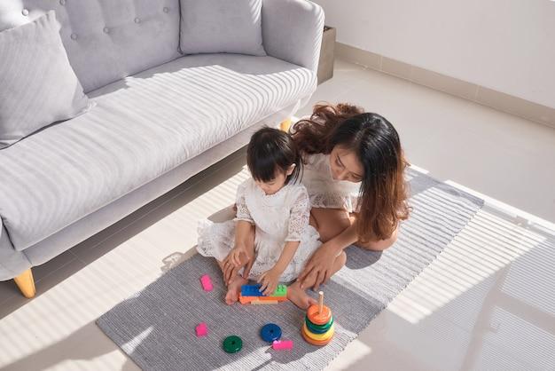 幸せな愛情のある家族。母と娘はおもちゃで遊んで楽しんでいます。居間の床に座ってあなたの教育をしている母と娘。