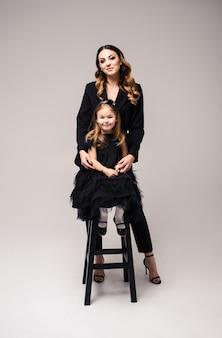幸せな愛情のある家族。灰色の背景に母と娘の子の女の子