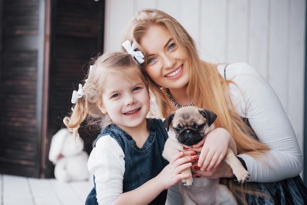행복한 사랑의 가족. 어머니와 그녀의 딸 아이 소녀 연주와 사랑스러운 퍼그 포옹