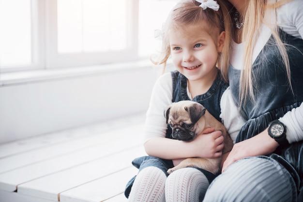 행복한 사랑의 가족. 어머니와 그녀의 딸 아이 소녀 재생과 사랑스러운 퍼그 포옹