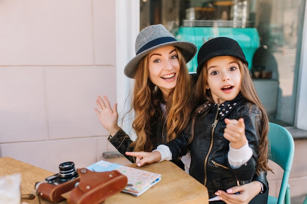 Счастливая любящая семья. мать и ее дочь сидят в городском кафе, удивленно глядя на камеру и девушку, показывающую путь. на столе лежит карта и фотоаппараты. настоящие эмоции, хорошее настроение ..