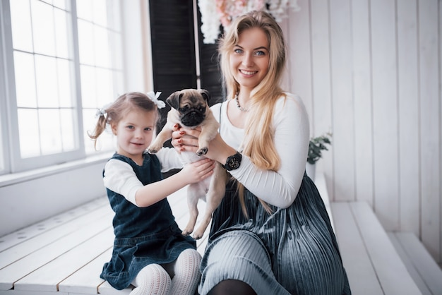 Happy loving family. mother and her daughter child girl playing and hugging adorable pug