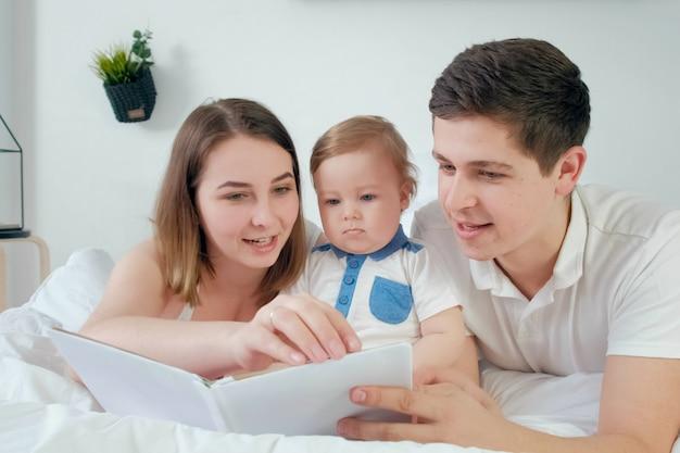 행복한 사랑하는 가족. 예쁜 젊은 엄마와 딸들에게 책을 읽어주는 데드