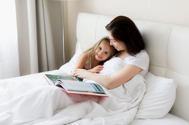幸せな愛情のある家族。かなり若い母親が娘に本を読んで