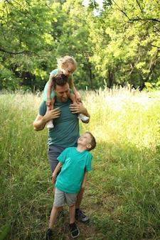 幸せな愛情のある父と2人の子供、息子と娘が遊んで抱き締める