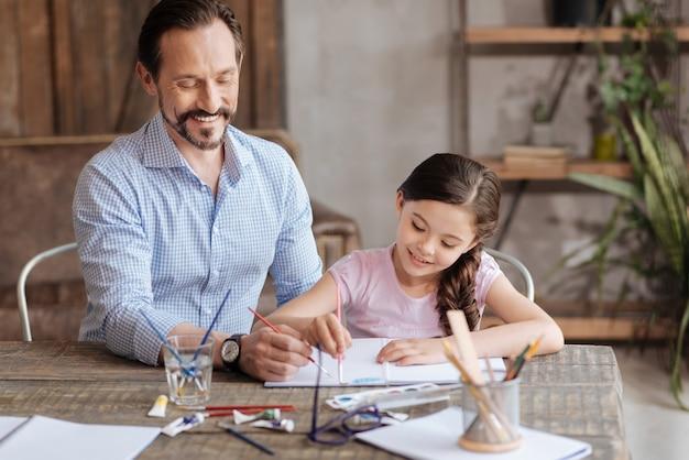 幸せな愛情のある父親は、彼の甘い小さな娘の隣に座って、彼女が両方ともインスピレーションを得ているように見えながら、水彩で青い空を描くのを手伝っています