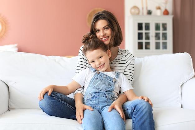 Счастливая любящая мама обнимает маленькую дочь, вместе проводят время дома.