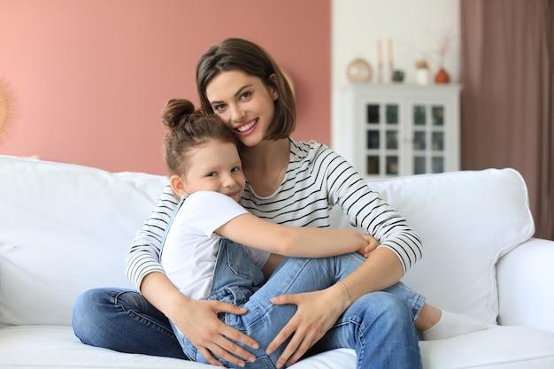 小さな娘を抱き締めて幸せな愛情のあるお母さん、家で一緒に時間を過ごします。