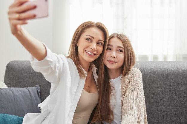 Счастливая любящая мама с дочкой-подростком сидит на диване и делает селфи на смартфоне, наслаждаясь свободным временем вместе дома