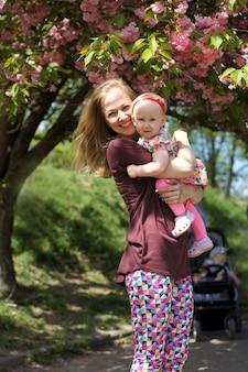 幸せな愛情のある母と娘が遊んで、抱き締めます。家族の散歩。一緒に夏の時間、太陽の光。母の日おめでとう。