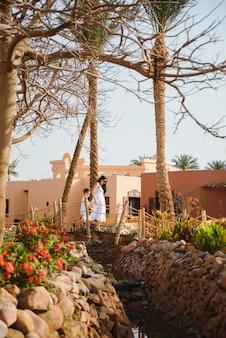 Счастливая любящая мать и сын. семейная прогулка возле пальм. пляжный отель в турции. с днем матери.