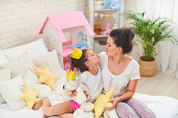 Happy loving mother and daughter play with crowns and cuddle on bed