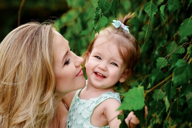 Happy loving mother and girl cuddling outdoor summer background.