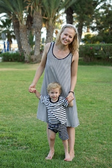 Happy loving mother and son playing and hugging. family walk near palms. turkey beach hotel. summer time together, sun light. happy mothers day.