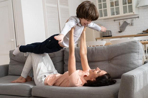 かわいい息子と幸せな愛情のある母親は飛行機を模倣します
