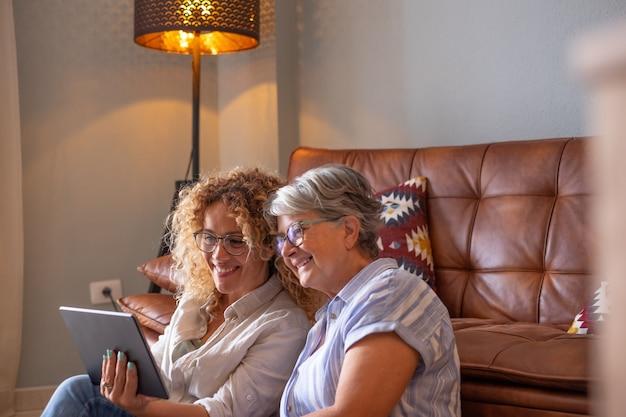 幸せな愛情のある年上の成熟した母と娘笑う思いやりのある笑顔幸せなシニア中年のお母さんが技術的なデバイスと一緒に時間を過ごして家で楽しんでいます