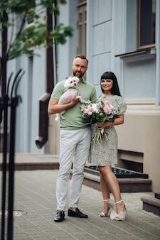 Счастливая любящая романтическая пара гуляет с собакой на открытом воздухе. девушка с букетом цветов и парень со щенком на свидании