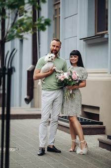 Happy loving romantic couple walking with pet little dog outdoor. girl with flowers bouquet and guy with puppy on dating
