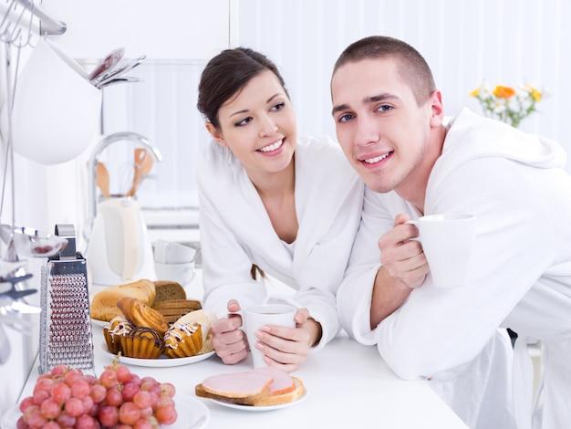 キッチンで一緒に朝食を食べている幸せな愛情のある若いカップル