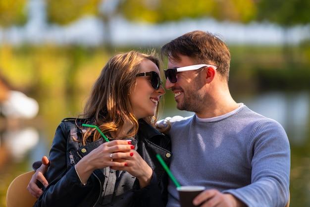 Счастливая любящая молодая пара в тесных объятиях, сидящая за столом в осеннем парке, вместе наслаждаясь кофе