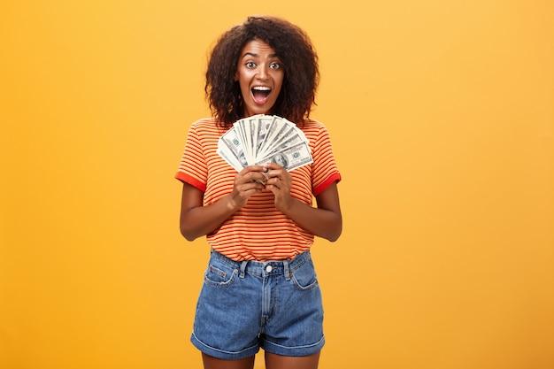 たくさんのお金を保持し、喜びから叫んで巻き毛の幸せな幸運なアフリカ系アメリカ人の若い女性