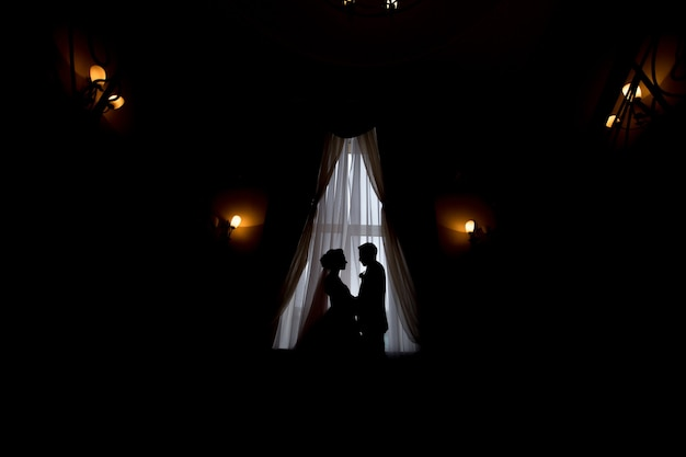 Happy luxury bride and groom standing at window light in rich room, tender moment