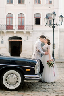Happy luxury wedding couple kissing and embracing near black retro car in old city center, ancient buildings on the background.