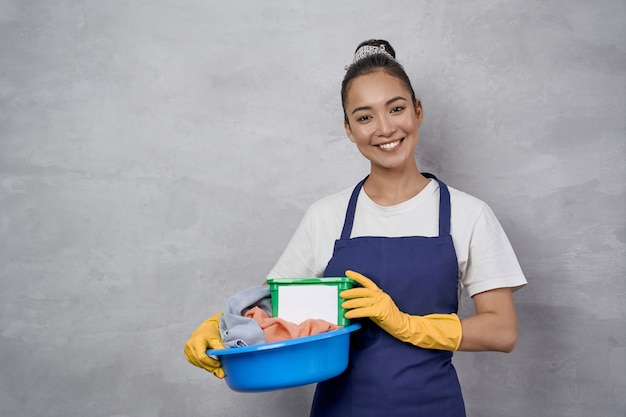 Happy maid woman in uniform holding basket with laundry and green plastic box with washing