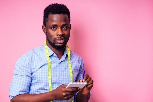 Счастливый мужской африканский дизайнер-конструктор, записывающий идеи в блокнот на розовом фоне в студии. красивая и молодая швея-портной с рулеткой
