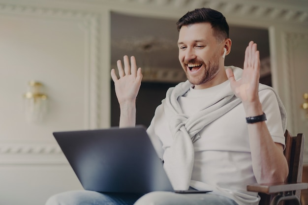 Счастливый блоггер-мужчина разговаривает с подписчиками, машет ладонями перед камерой портативного компьютера, выражает радость, разговаривает во время онлайн-трансляции, использует беспроводные наушники, наслаждается дружеской беседой, слышит хорошие новости