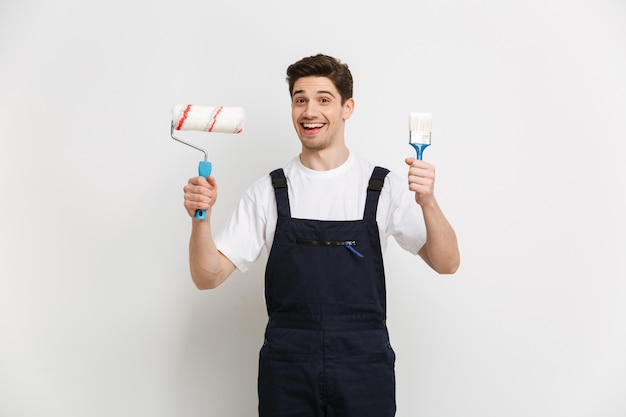 Счастливый мужчина-строитель держит рулон краски и кисть над серой стеной