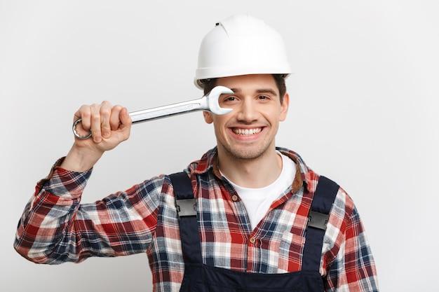 Счастливый мужчина-строитель в защитном шлеме развлекается с гаечным ключом над серой стеной