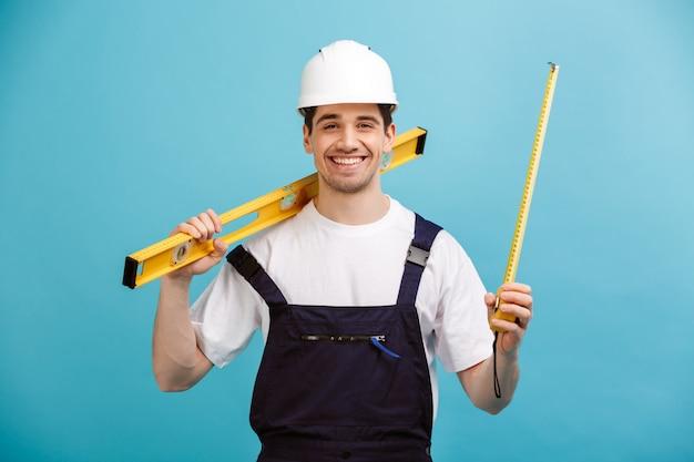 Счастливый мужчина-строитель в защитном шлеме, держа инструмент уровня и измерительную ленту над синей стеной