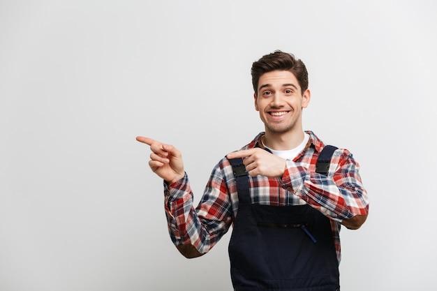灰色の壁を越えて2つの人差し指でさして幸せな男性ビルダー