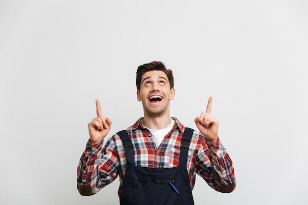 Счастливый мужчина-строитель, указывая двумя указательными пальцами и глядя на серую стену
