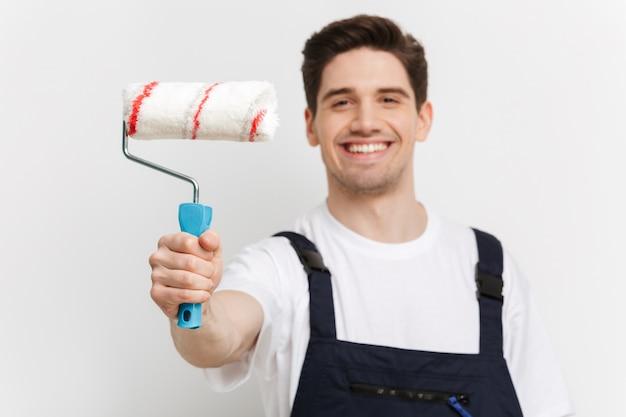 Счастливый мужчина-строитель показывает рулон краски над серой стеной