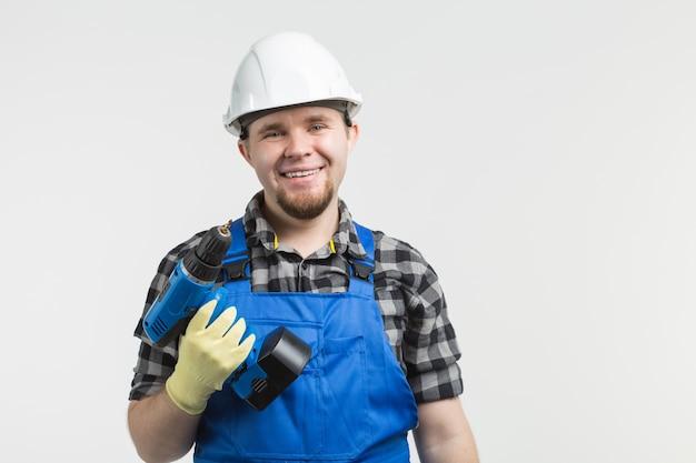Счастливый мужчина-строитель, стоящий на лестнице с дрелью перед окном