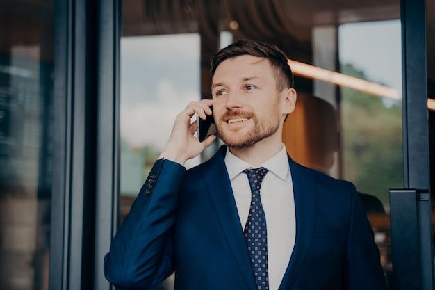 スマートフォンを介してプロジェクトの結果についての良いニュースを受け取り、オフィスビルのガラスの玄関ドアの隣に立っている間、笑顔で喜んで聞いて、青いスーツを着た幸せな男性のビジネスオーナー