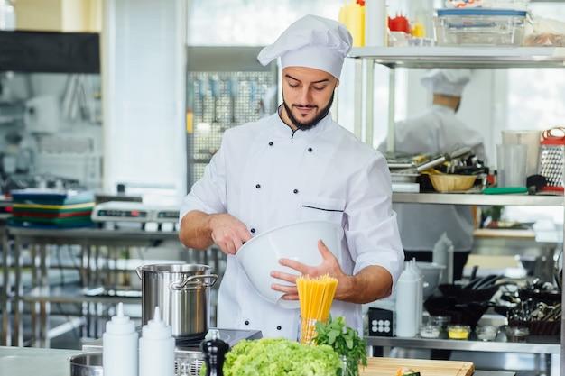 Счастливый мужской шеф-повар готовит на кухне ресторана.