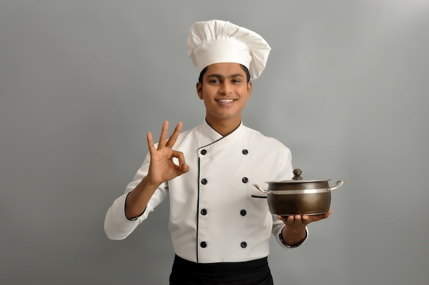 Happy male chef dressed in uniform holding pot with showing ok gesture with one hand