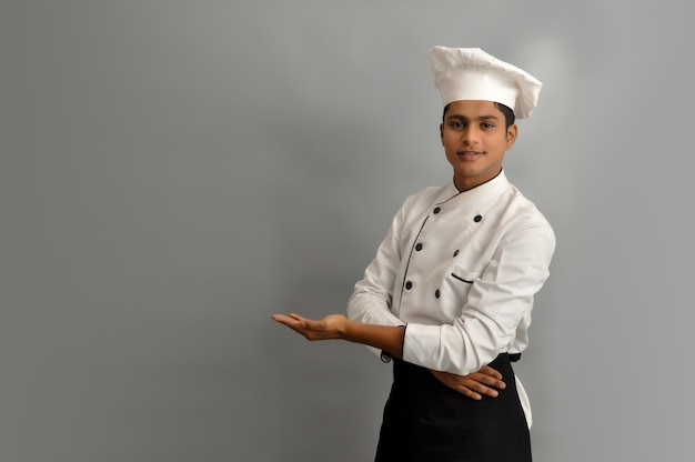 Happy male chef dressed in uniform holding something on palm of hand over