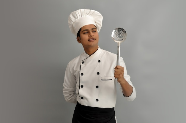 Happy male chef dressed in uniform holding steel skimmer and looking
