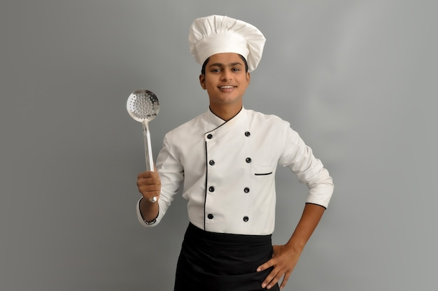 Happy male chef dressed in uniform holding steel skimmer