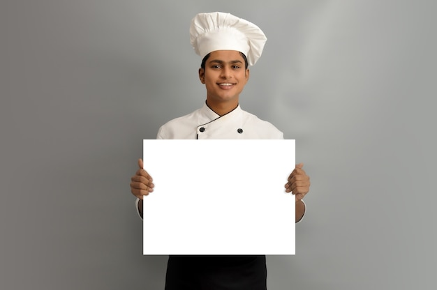 Happy male chef dressed in uniform holding white advertising banner good poster for ad